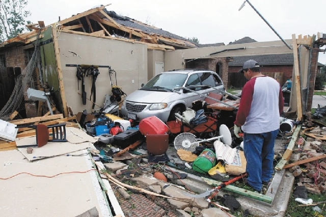 Pete Alaniz looks for items to salvage Thursday after a tornado hit his home in Cleburne, Texas. His family of four and three dogs hid in his closet while the tornado destroyed their home. The vio ...