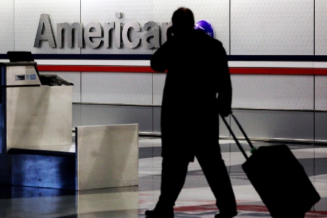 In this 2011 file photo, a passenger walks through an American Airlines baggage claim area at O'Hare International Airport in Chicago. American Airlines said Thursday that people carrying just a p ...