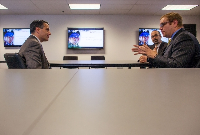 From left, Gov. Brian Sandoval, Vice President Operations of BMM Travis Foley and BMM's Chief Operating Officer Mike Dreitzer, talk during Sandoval's tour of the gaming lab at 815 Pilot Road, suit ...