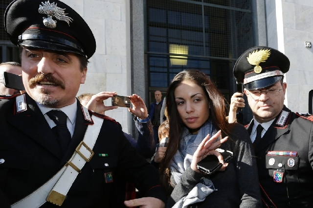 Karima el-Mahroug's is escorted outside Milan's court by two Carabinieri police officers after giving her testimony at the trial of three former Berlusconi aides accused with procuring her and oth ...