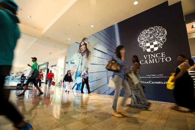 Shoppers walk past the future Vince Camuto storefront inside the Fashion Show mall on Thursday. Local shopping centers on the Strip are getting ready to welcome the rest of their industry as the I ...