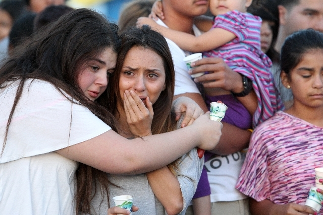 An aunt of 15-year-old Marcos Vincente Arenas, Karina Arenas, gets a hug from an unidentified friend at a vigil for the slain teen at Firefighters Memorial Park.