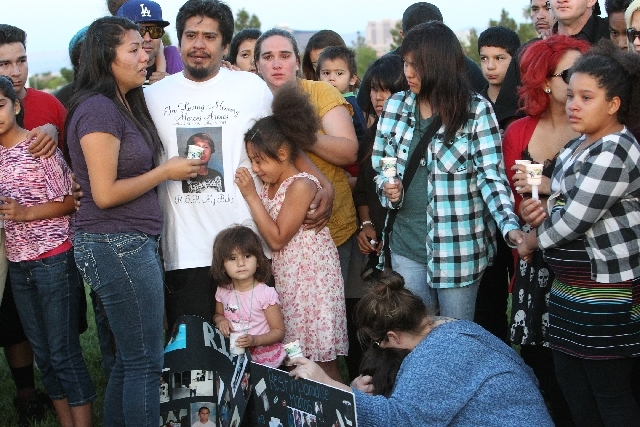 Family members and friends of 15-year-old Marcos Vincente Arenas, including Marcos' father, Ivan Arenas, second from left in a white T-shirt, attend a vigil for their slain loved one at Firefighte ...