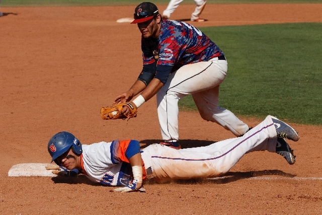 Bishop Gorman's Jerrel Latham slides safely back into third base under the tag by Julian Burrola of Coronado in the Division I baseball state final at College of Southern Nevada.