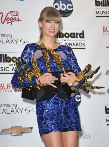 Taylor Swift poses backstage with an armload of awards at the Billboard Music Awards on Sunday at the MGM Grand Garden. She won eight awards, including top artist and album of the year.