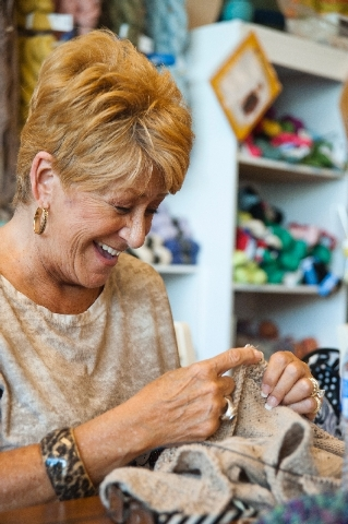 Diane Geisler shares a laugh during a class at the Sin City Knit Shop. In addition to classes, the community at the shop has crocheted countless scarves and sweaters and created Christmas and birt ...