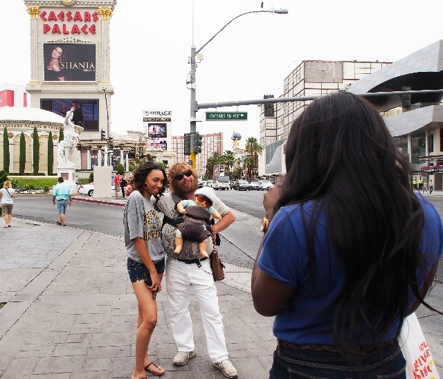 """Brian Petre, portraying Alan from """"The Hangover,"""" poses with Tivona Batieste, of Los Angeles, as her friend Jennifer Okafor, also of Los Angeles, takes their photo at Caesars Palace."""