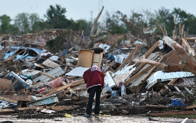A resident looks through the rubble of a destroyed home Tuesday, one day after a tornado moved through Moore, Okla. Emergency crews searched the broken remnants of the Oklahoma City suburb for sur ...