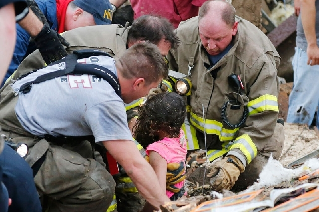 A child is pulled from beneath a collapsed wall at Plaza Towers Elementary School Monday after a tornado struck the school in Moore, Okla. The tornado, as much as a mile wide with winds up to 200  ...