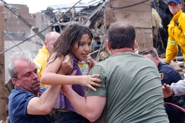 A girl is pulled from the rubble of Plaza Towers Elementary School and passed along to rescuers after a tornado struck the school Monday in Moore, Okla.
