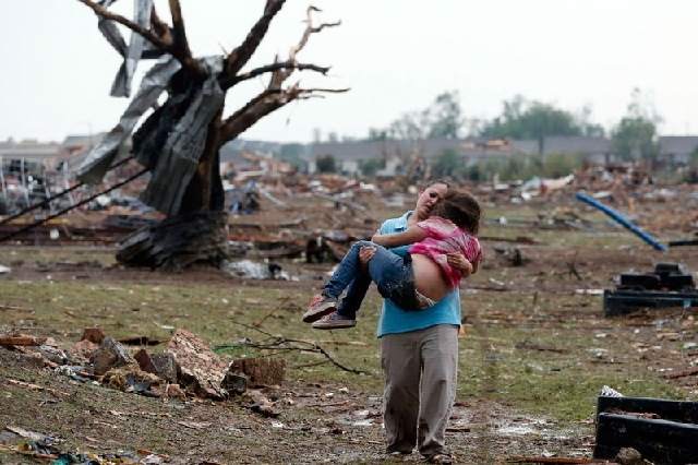 A woman carries a child through a field Monday near the collapsed Plaza Towers Elementary School in Moore, Okla.