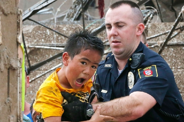 A boy is pulled from beneath a collapsed wall at the Plaza Towers Elementary School Monday after a tornado struck the school in Moore, Okla.