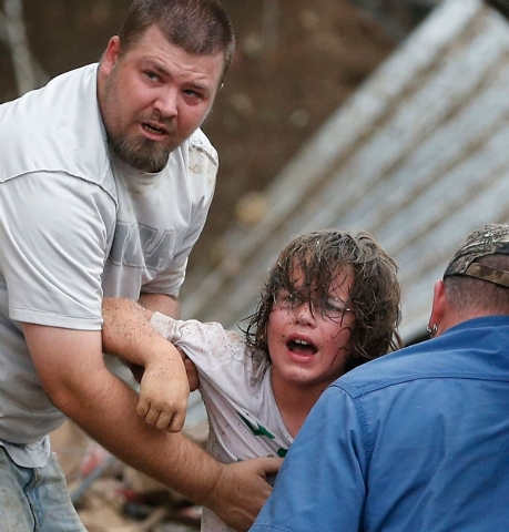 A child calls to his father after being pulled from the rubble of Plaza Towers Elementary School Monday after a tornado struck the school in Moore, Okla.