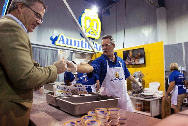 Paul Agamaite , center, passes out Auntie Anne's pretzels on Tuesday to conventiongoers at the International Council of Shopping Centers' annual convention, RECon. Franchise businesses like Auntie ...