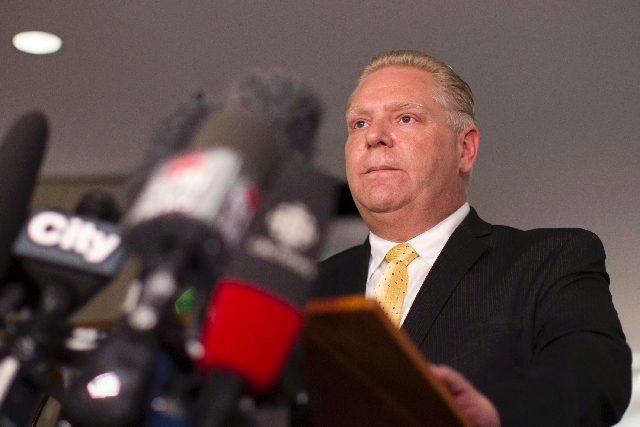 Toronto City Councillor Doug Ford reads a statement to journalists at Toronto's city hall on Wednesday as he details how the allegations surrounding his brother, Mayor Rob Ford, have affected his  ...