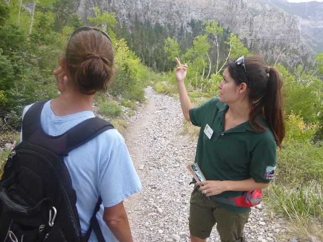 Trail host volunteer Christa Ward points out landscape features to a hiker on the Cathedral Rock Trail last summer. Ward and 19 other trail hosts aim to help guide visitors, maintain trails and pr ...