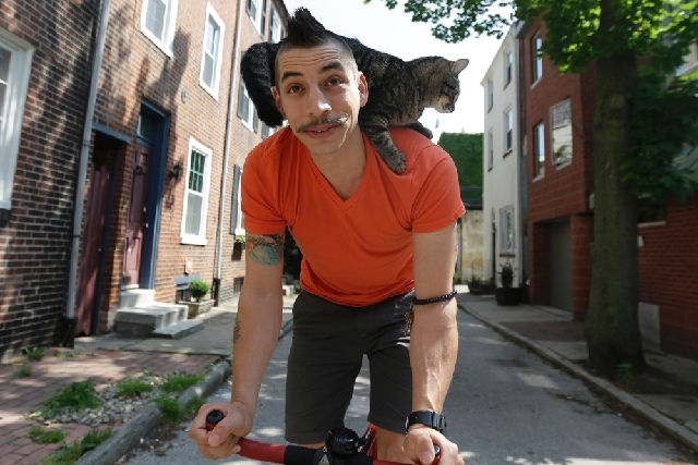Bicyclist Rudi Saldia and his cat Mary Jane pose for a portrait during an interview with the Associated Press in Philadelphia. Saldia often buzzes around Philadelphia with his year-old feline Mary ...