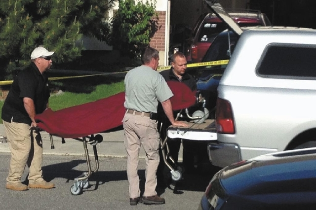 Medical examiner officials remove the body of one of the victims Thursday as law enforcement officials from Davis County, Utah, investigate the deaths of two young boys in West Point. An older bro ...