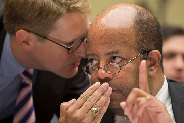 J. Russell George, the Treasury inspector general for tax administration, right, talks with a member of his staff on Capitol Hill in Washington on Wednesday. George testified before the House Over ...