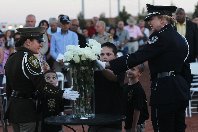 The children of Metro Police Officer Trevor Nettleton, from left, Carson, Lorenzo, and Gage place a flower in his tribute and memory during the annual Southern Nevada Law Enforcement Memorial serv ...