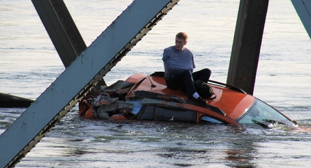 A man is seen sitting atop a car that fell into the Skagit River after the collapse of the Interstate 5 bridge there minutes earlier Thursday in Mount Vernon, Wash.