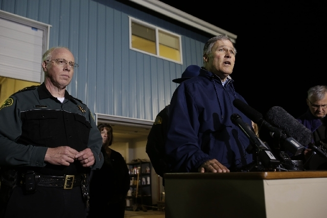 Washington Governor Jay Inslee, right, talks to reporters about the failure of the Interstate highway bridge crossing the Skagit River in Mt. Vernon on Thursday, dumping two vehicles into the wate ...