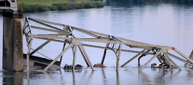 Partially-submerged vehicles lie in the debris of the collapsed portion of the Interstate 5 bridge in the Skagit River on Friday in Mount Vernon, Wash. A truck carrying an oversize load struck the ...
