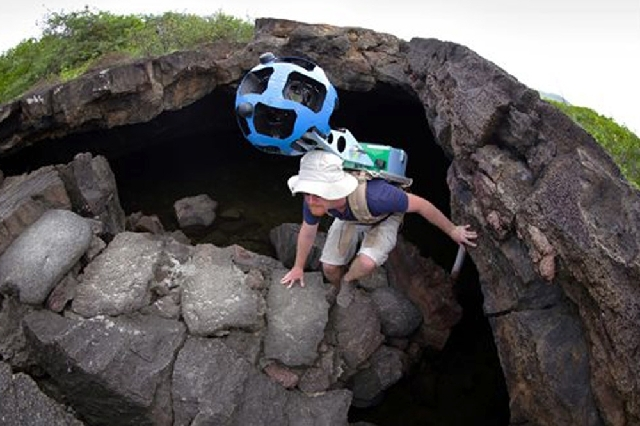 In this photo provided by Google, Daniel Orellana of the Charles Darwin Foundation climbs out of an Isabela island where he was collecting imagery on the Galapagos. The lava landscapes found on th ...