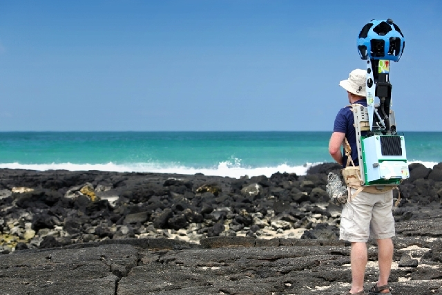 In this May 2013 photo provided by Google, Daniel Orellana of the Charles Darwin Foundation collects seashore imagery with the Street View Trekker at the Los Humedales wetland area on Isabela Isla ...