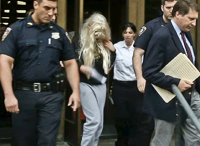Actress Amanda Bynes, center, wearing sweats and a blonde wig, is escorted after a Manhattan criminal court appearance on Friday in New York.