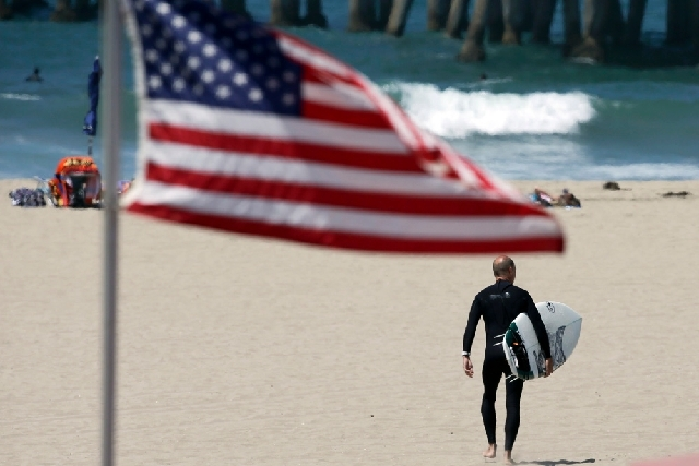 A surfer carries his board on the beach in Huntington Beach, Calif., on Friday. AAA expects 31.2 million Americans to hit the road this weekend, virtually the same number as last year. Throw in pl ...