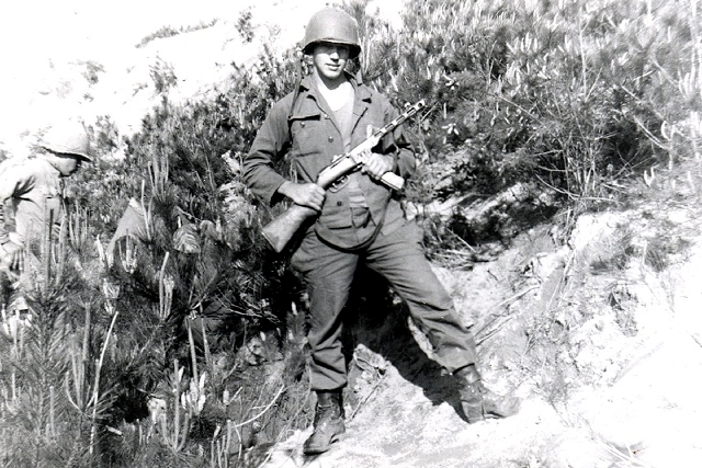 "Pvt. Warren ""Gene"" Sessler holds a captured Russian-made submachine gun on July 13, 1953, near Outpost Harry."
