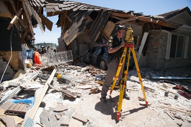 Utah Highway Patrol Sgt. Lamar Heaton uses a total station to create a scale diagram of the accident scene after an RV crashed into several townhomes on Friday in St. George, Utah.