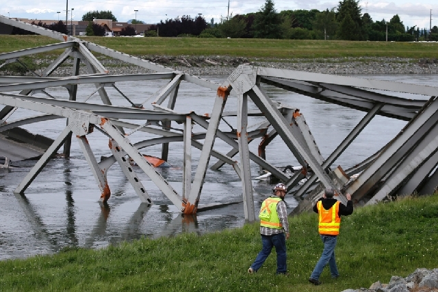 Workers walk past the collapsed portion of the Interstate 5 bridge at the Skagit River on Friday in Mount Vernon, Wash. A truck carrying an oversize load struck the four-lane bridge on the major t ...