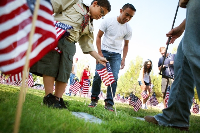 Cub Scout Elijah Harris, 8, left, and Christian Aranaydo, center, place U.S. flags at grave sites at Southern Nevada Veterans Memorial Cemetery in Boulder City on Saturday. The two were among seve ...
