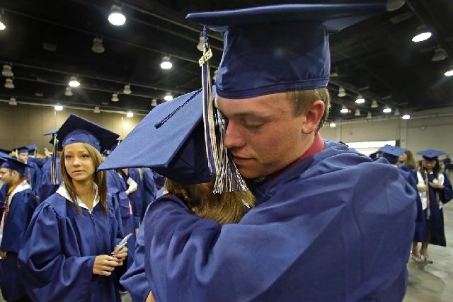 Southmoore High School senior Jake Spradling, hugs a classmate as they get ready to attend their commencement ceremony in Oklahoma City on Saturday, five days after a tornado destroyed a large swa ...