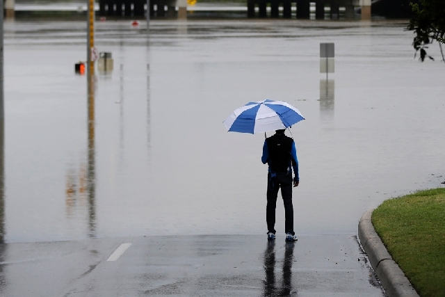 A man surveys floodwaters caused by heavy rains Saturday in San Antonio. The city has received torrential rains since Friday evening and officials say numerous roads have been closed because of fl ...