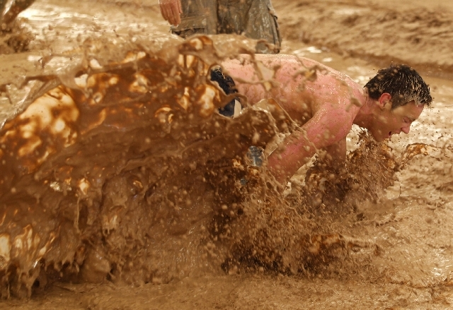 Participants make their way through the Mud Mayhem obstacle Saturday during the Badass Dash at the South Point. The Badass Dash, billed as a worldwide adventure race and obstacle course challenge, ...