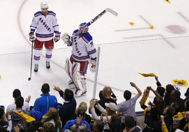 As Boston Bruins fans celebrate, New York Rangers goalie Henrik Lundqvist (30) and center Derick Brassard skate downice after losing 3-1 to the Bruins, eliminating the Rangers from the NHL playoffs.