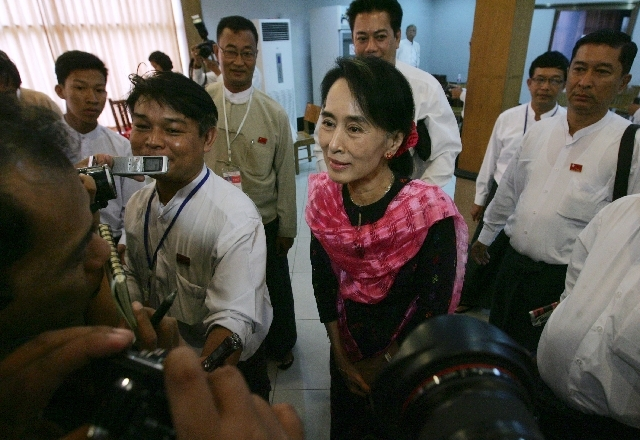 Myanmar Opposition Leader Aung San Suu Kyi, center, talks to journalists as she attends Central Executive Committee (CEC) meeting of her National League for Democracy party at a restaurant in Yang ...