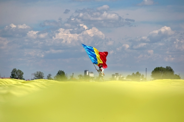 A man holding a Romanian flag stands at the edge of a huge version of the flag, on the Clinceni Airfield, south of Bucharest, Romania on Monday.