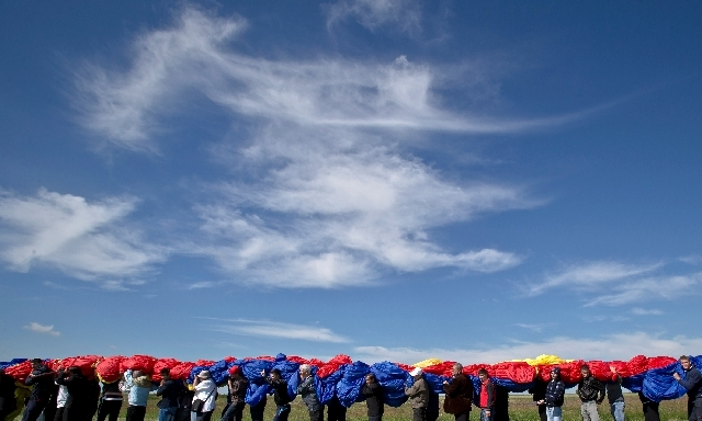 Romanians carry a huge national flag on the Clinceni Airfield, south of Bucharest, Romania on Monday.