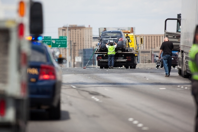 A tow truck worker checks a car involved in a five-vehicle crash including two semitrailers on the Interstate 15 northbound just past Sahara Avenue in Las Vegas on Tuesday.