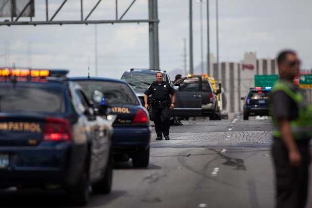 A Nevada Highway Patrol officer walks by the scene of a five-vehicle crash including two semitrailers on the Interstate 15 northbound just past Sahara Avenue in Las Vegas on Tuesday. The crash shu ...