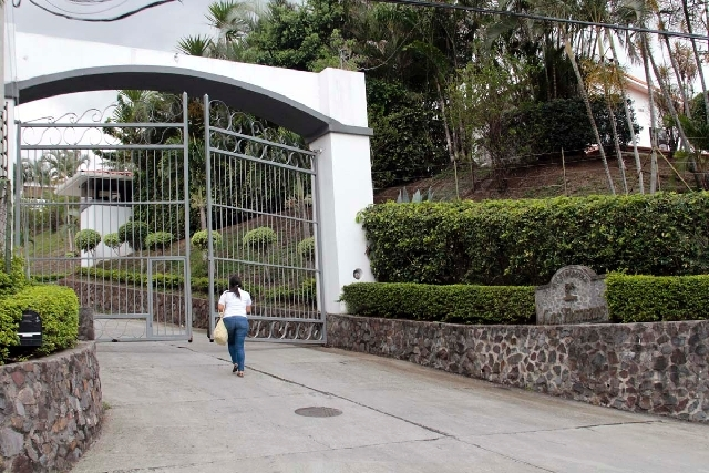 A woman walks towards the entrance to Residencial Las Terrazas in the mountains near Santa Ana, Costa Rica, on Tuesday. Costa Rican police raided one of residences of Las Terrazas as well as two o ...