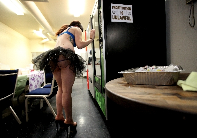 A dancer looks through vending machine options backstage before performing at The Horse, the site of the former Crazy Horse Too, on Industrial Road in Las Vegas on Thursday, May 30, 2013. The stri ...