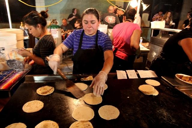 Siomara Padilla flips handmade tortillas at the Quality Food Service stand at First Friday.