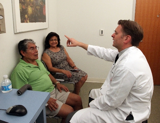 Dr. Ryan Walsh works with patient Jose L. Martinez while Martinez's wife, Irma, looks on during an appointment at the Cleveland Clinic Lou Ruvo Center for Brain Health.