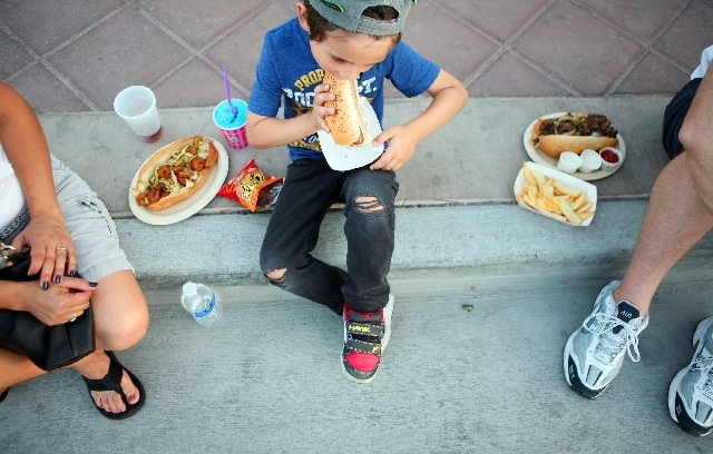 Cole Massey eats a hot dog with his family during May's First Friday in Las Vegas. The monthly art festival features some 35 food vendors offering silders, kabobs, sweet potato fries, pizza, sandw ...