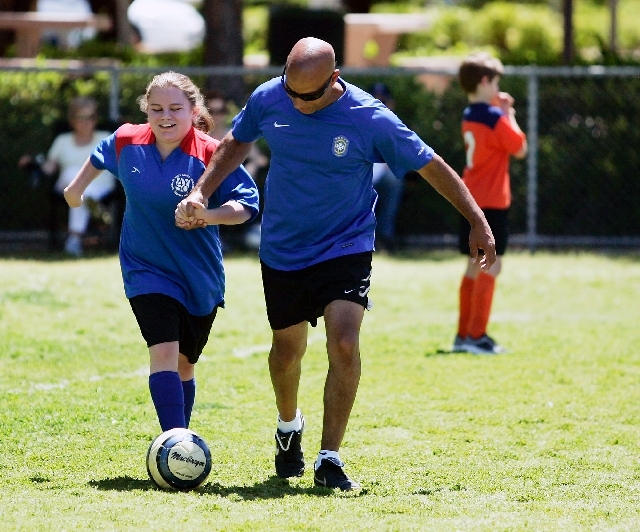 Kylie, left, kicks the ball with the aid of her father, David, during a VIP (Very Important Player) soccer game at The Crossing Park in Summerlin, May 11. American Youth Soccer Organization launch ...